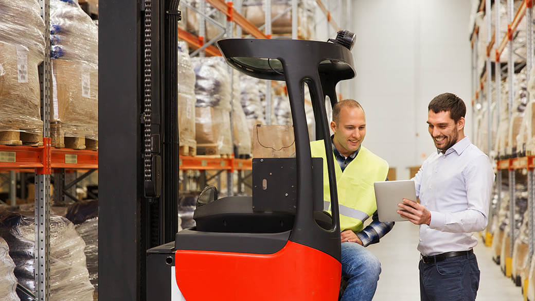Men in a warehouse talking, looking at a tablet, one of them sitting in a forklift