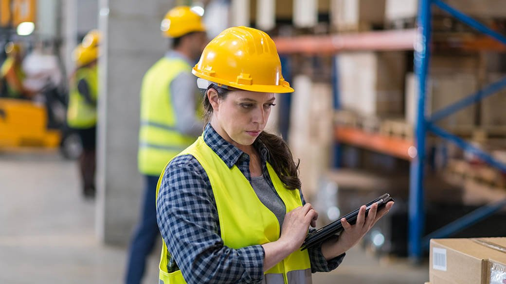 woman in a warehouse holding a tablet