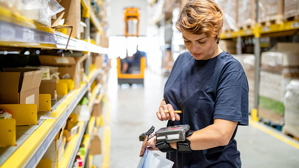 woman in a warehouse looking at a barcode reader she is wearing