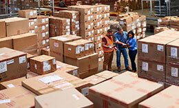 Three people at work in a large warehouse full of boxes