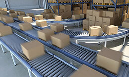 Boxes and packed goods moving on conveyor belt inside a large distribution warehouse building, with plenty of cardboard boxes and goods stacked on pallets on the background